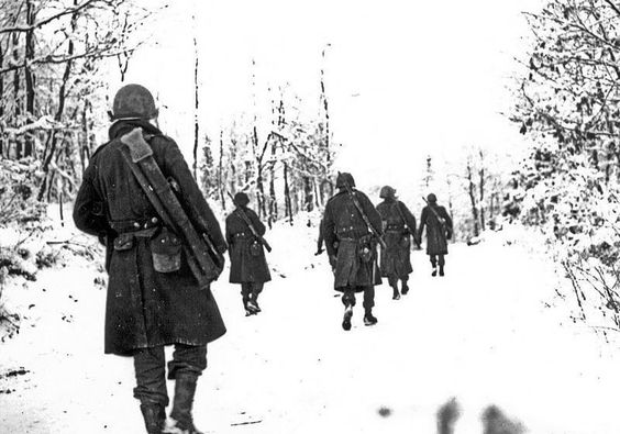 American soldiers of the 84th Division moving up to new positions through the snow covered countryside in Belgium