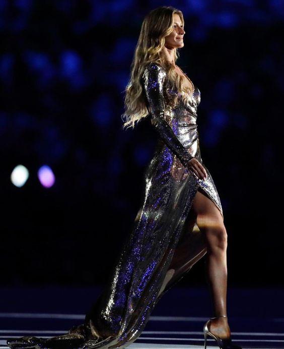 """Vestindo um deslumbrante vestido dourado, criado por Alexandre Herchcovitch, ela desfilou ao som de """"Garota Ipanema"""" de Tom Jobim,…"""