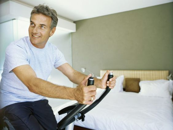 A man riding an exercise bike in the bedroom.