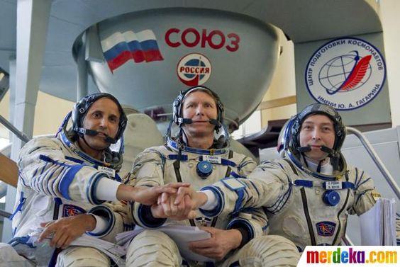 Astronot dari AS Joseph Acaba (kanan) dan kosmonot Rusia Gennady Padalka (tengah) dan Sergei Revin berfoto di depan mock-up pesawat ruang angkasa Soyuz pada sesi latihan di Star City space centre, Moskow.