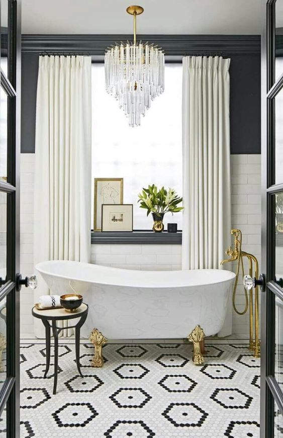 Black and white elegant and luxurious bathroom with crystal chandelier, clawfoot tub, and gold accents. Hexagon black and white tile flooring plays a starring role! #blackandwhite #elegantdecor #bathroomdecor