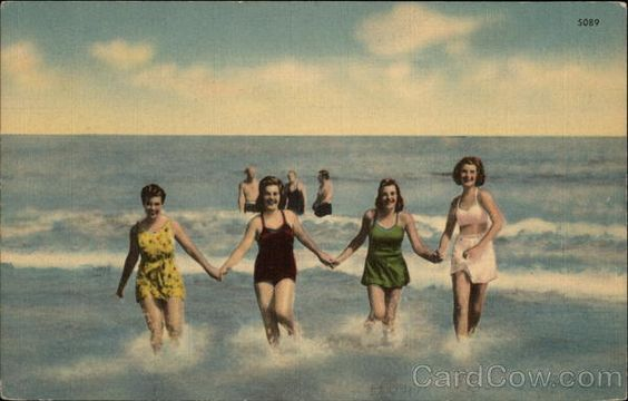 Four Women in Swimwear Holding Hands in the Surf Swimsuits & Pinup