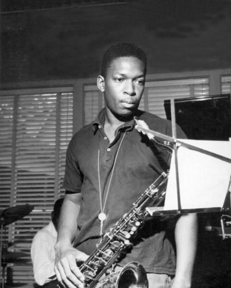 Jazz saxophonist John Coltrane poses for reads music on a music stand in 1962