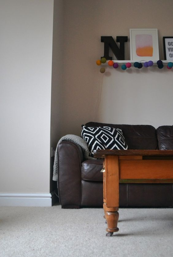 Living room renovation. Taupe walls, wood, black and white geometric cushion, picture ledge and colourful ball lights.