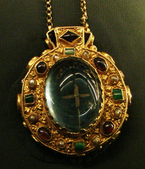 The Talisman of Charlemagne, c. 768-814. Two large cabochon sapphires - one oval, one square - enclose holy relics (what are supposed to be a remnant of the Holy Cross and a small piece of the Virgin's hair, visible only when looking through the oval sapphire at the front of the medallion.) The other gemstones are garnets, emeralds, and pearls.