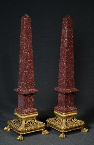 Pair of antique obelisks in dark red porphyry with square gilt bronze pierced and chiselled scrolls and flowers bases (h. 46 cm).