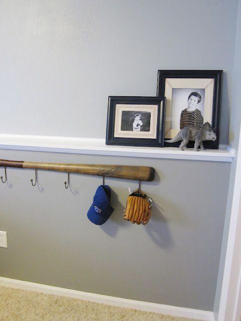 baseball hooks in back hallway with black shelf above and baseball pics of boys