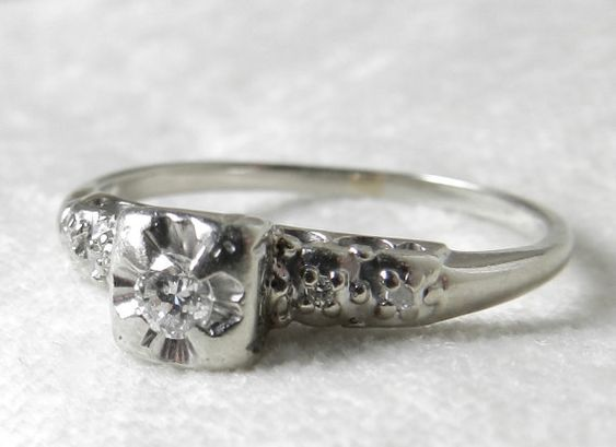Classic vintage engagement ring! Art Deco engagement ring with total diamond weight of a quarter carat 0.15 Ct. in 14K white gold. Very romantic 1940s period piece and diamonds are full of fire making this a unique diamond engagement ring. Measuring 3.1mm, the center diamond is prong set and flanked by four smaller diamonds of 1.1mm each, all an estimated S12 (slight crystal inclusions visible under 10x magnification) and in the early to mid near colorless range.. Made from solid 14K (marked…