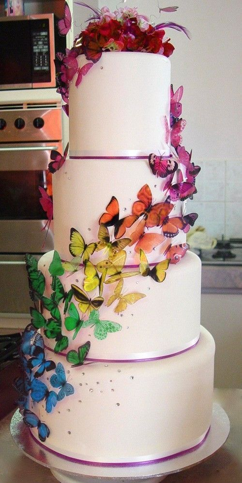 Rainbow butterfly wedding cake- The best way to get a cheap wedding cake is to order the cake from a bakery (DO NOT TELL THEM ITS FOR A WEDDING! or the price goes up!) and have a friend decorate it for you