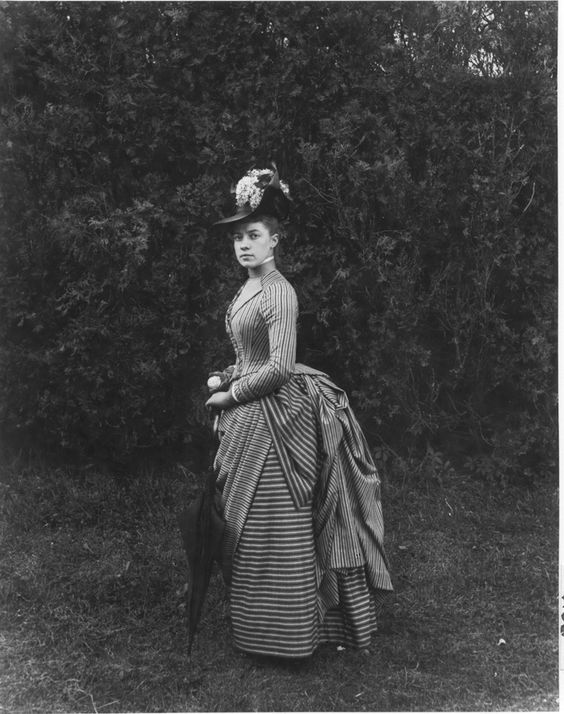 """Twenty-two-year-old Miss E. Alice Austen poses in her Sunday best - a smart overskirt and a hat decorated with white lilacs. She holds a parasol and a silver change purse. Photo taken in June 1888 by Captain Oswald Muller."" #Victorian #fashion #women #photography:"