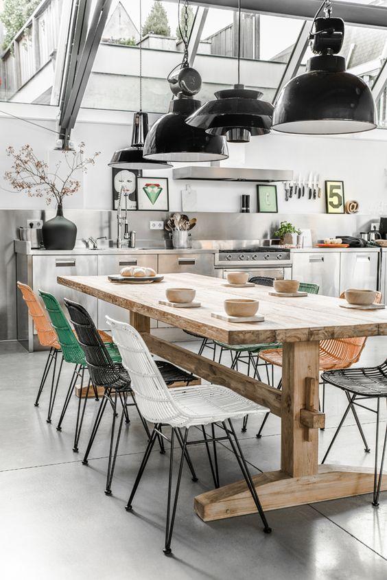 #reforma #cocina abierta sólo muebles bajos de acero inoxidable, mesa de madera con sillas patas metálicas y respaldos de varios colores, suelo de microcemento.: