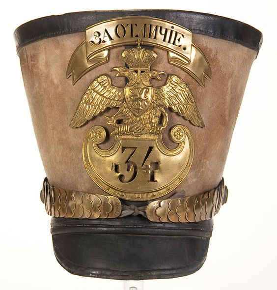 AN IMPERIAL RUSSIAN INFANTRY SHAKO, circa 1840. Enlisted man's issue pattern of felt, with black leather crown, band and visor. Has brass bandeau pierced with Cyrillic inscription FOR DISTINCTION over an eagle plate with regimental number 34 pierced through the Amazon shield. Complete with brass chin scales. Lined with linen and leather. - Jackson's International Auctioneers and Appraisers