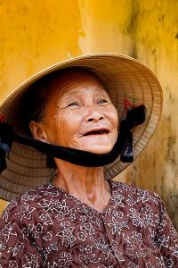 Portrait of an elderly woman wearing a traditional conical hat