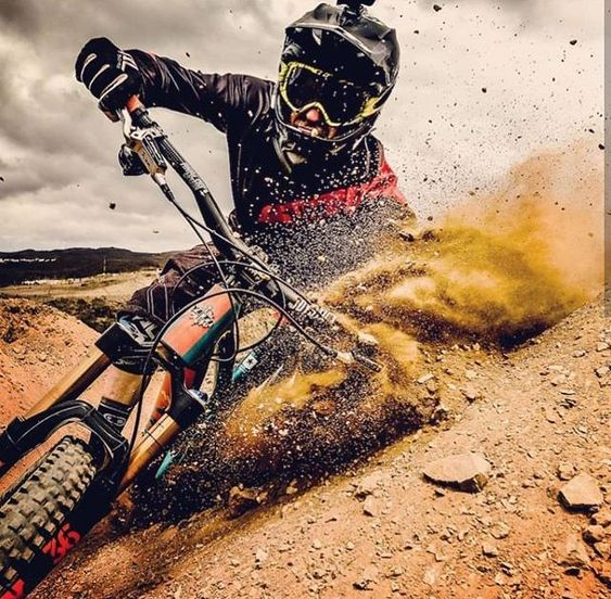 Close up photo of a downhill mountain biker hitting the dirt.