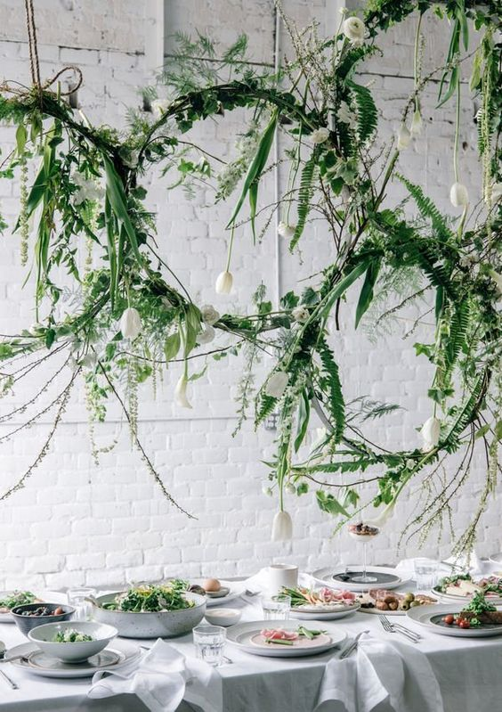 Hanging hula hoop chandeliers covered in greenery for wedding table idea