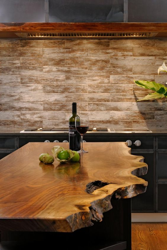 This unique kitchen island features a top made from live-edge walnut, bringing an organic element into this modern, custom space. On the cooktop wall, cabinetry is constructed from hot-rolled steel panels, and rough-hewn walnut carries onto the custom hood.: