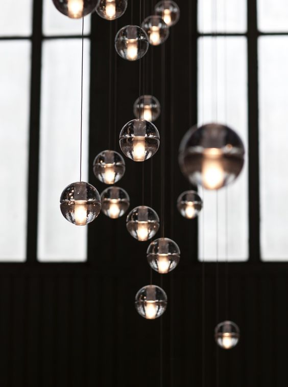 "14 Chandelier from Bocci. Irregular, handmade glass spheres can be combined in infinite arrangements. ""Light interacts with the bubbles and imperfections of the cast glass to produce a glow reminiscent of small candles floating within spheres of water. Cast glass is an organic process, imperfect by nature, and each 14 series pendant is handmade; thus, every piece produced is unique."""