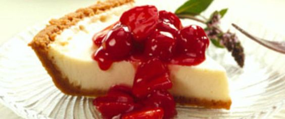 A delectable dessert - vanilla cheesecake with cracker crust base, mouth-watering cherry-berry topping and pure delight in every bite!