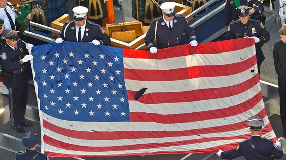 ...U.S. flag recovered from the 9/11 attacks is displayed by New York City police officers and firefighters at the 9/11 Memorial ceremony...