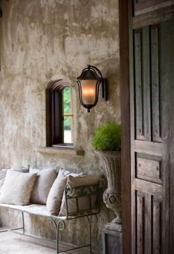 Rustic farmhouse exterior entry with bench and pillows. European Farmhouse and French Country Decorating Style Photos. #rusticdecor #frenchcountry #europeanfarmhouse #frontdoor