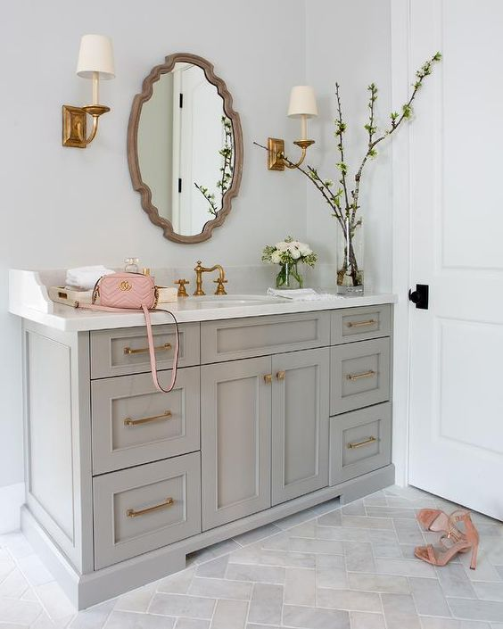 This chic gray bathroom is lit by antique brass sconces fixed to a pale gray painted wall on either side of a French vanity mirror.
