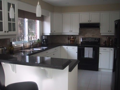 Kitchen with white cabinets and black appliances counter for Black kitchen cabinets with white appliances