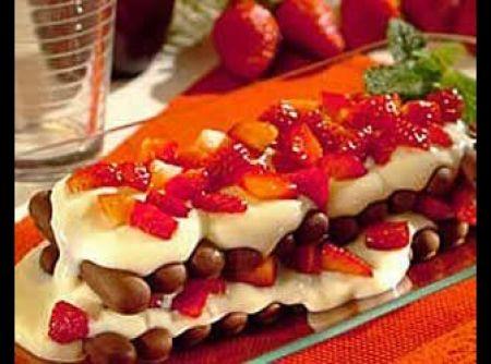 Receita de Pavê de Morango com Palitos de Chocolate - ½ lata de leite condensado, 2 ½ xícaras (chá) de leite, 2 colheres (sopa) cheias de amido de milho, 1 embalagem de creme de leite (200ml), 1 colher (chá) de essência de baunilha, 1 caixinha de morango picado (300g), ½ xícara (chá) de açúcar, 2 embalagens de Palitos ZABET Chocolate