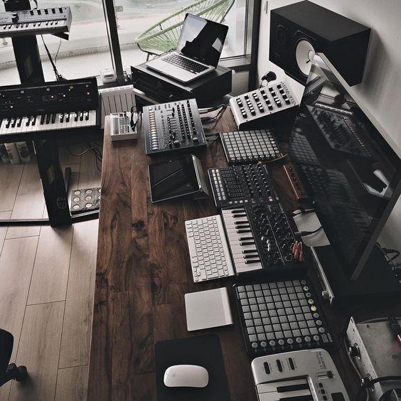 Sala com mesa à direita com diversos equipamentos de produção musical. Entre eles dois controladores de 64 pads, um controlador de faders e knobs, um controlador com teclas e knobs, uma máquina de ritmos Roland TR-8.