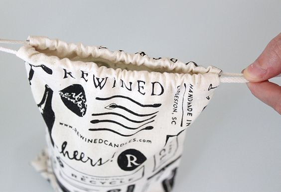 Packaging with illustrative detail including cloth bags designed by Stitch for craft candle brand Rewined.