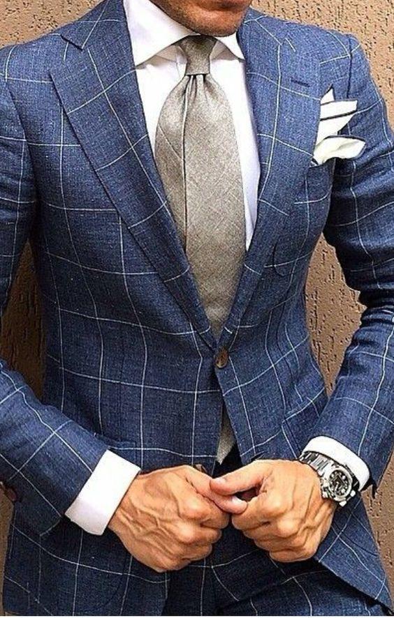 Acheter la tenue sur Lookastic: https://lookastic.fr/mode-homme/tenues/blazer-chemise-de-ville-pantalon-de-costume/19230   — Chemise de ville blanche  — Pochette de costume blanc  — Cravate gris  — Blazer en laine à carreaux bleu  — Montre argenté  — Pantalon de costume à carreaux bleu