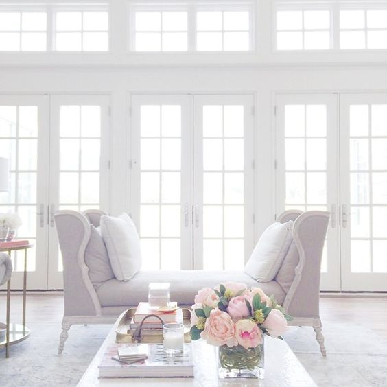 floor-to-ceiling windows shedding soft white light on gentle feminine colors of lilac and rose
