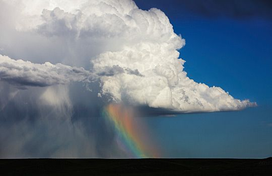 Cumulonimbus cloud over sheets of rain & rainbow, Colo