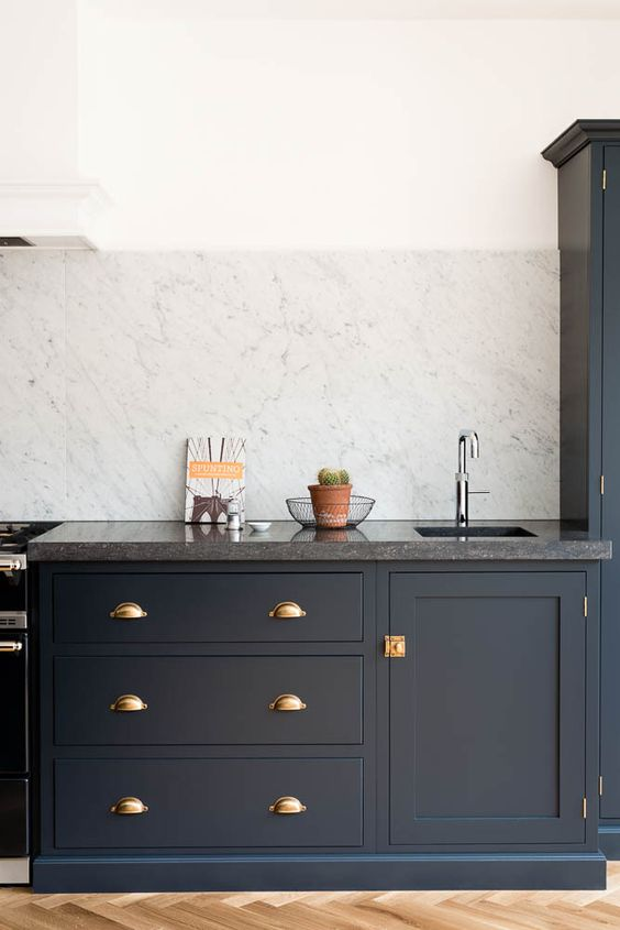 Belgian Blue Fossil worktops and a huge Carrara marble splashback make this Shaker kitchen very special