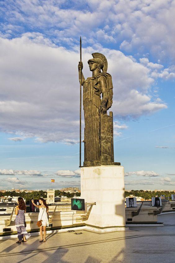 La Minerva del Círculo de Bellas Artes dominando Madrid. La estatua que domina desde lo alto del Círculo de Bellas Artes es una representación de Minerva, la Atenea romana, diosa de la sabiduría, las artes y la guerra. Todo un icono situado en la azotea del inmueble, uno de los mejores miradores de la capital.