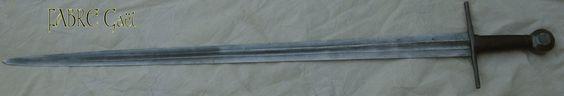 Epée de guerre entre le XIème et le XIVème siècle   Lame, garde et pommeau, feuilletés à plus de 700 couches. Gouttière d'allègement forgée.  Lame de 80 cm de longueur et de 5 cm de largeur au talon.  Fusée en chêne recouvert de cuir bouilli. Poids: 1100 grammes
