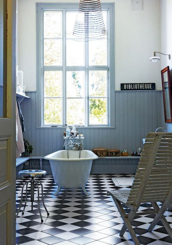 Roll top bath and black and white chequered floor in a Swedish artist's home in a former school house. Photo: Martin Löf.