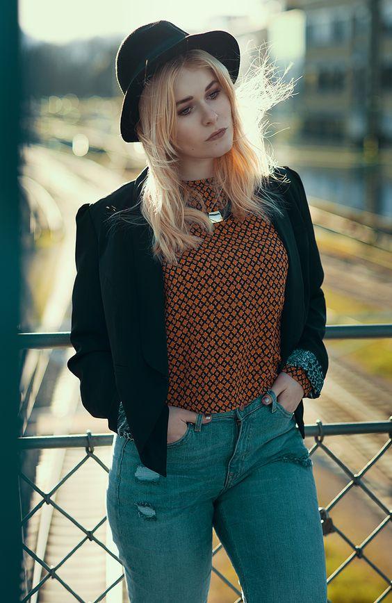 Influencer Christina Key trägt einen schwarzen Hut, eine orangene Retro Bluse und einen lässige Jeans