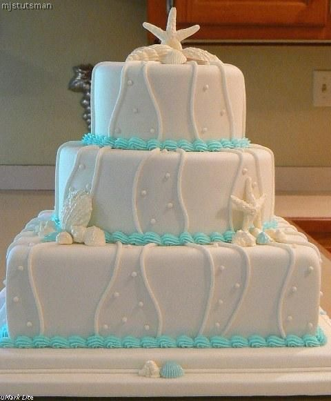 """Blue Seashell Wedding Cake - Another version of a cake I have already made.  White chocolate seashells dusted with super pearl dust.  White-flavored cake layers covered with Pettinice fondant (6"""", 9"""" and 12"""").  Light blue shells made from fondant."""