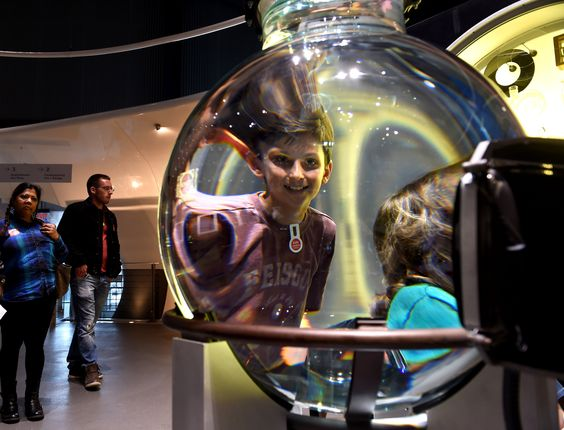 Looking through a giant water lens during a tour of the Innovation Center at the Corning Museum of Glass. Southern Tier Travel