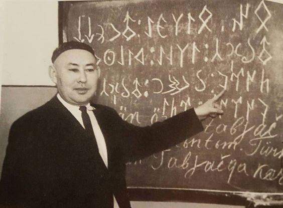 Kazakistan'ın ünlü Türkologlarından Gubeydulla Aydarov, tahtaya yazdığı Tonyukuk yazıtından bir bölüm.. Eliyle gösterdiği tamgalar da ''Türk'' sözcüğünü ifade etmektedir.: