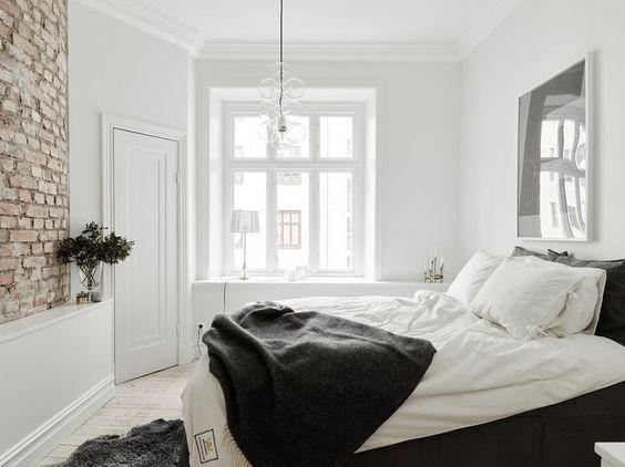 Chłodny wystrój tej sypialni z łóżkiem w grafitowym pokrowcu ociepla odkryta cegła na jednej ze ścian. Ściana w dodatku jest łukowata, dzięki czemu zyskuje na atrakcyjności architektura wnętrza. Dobudowany do niej ozdobny gzyms służy za półkę na dekoracje.
