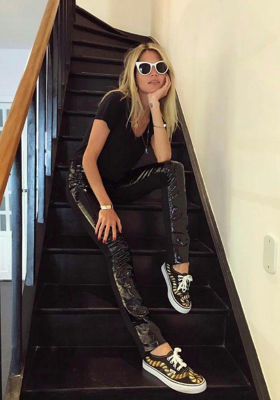óculos de gatinho com aramação branca, blusa preta, calça de vinil, tênis preto estampado, look todo preto, all black