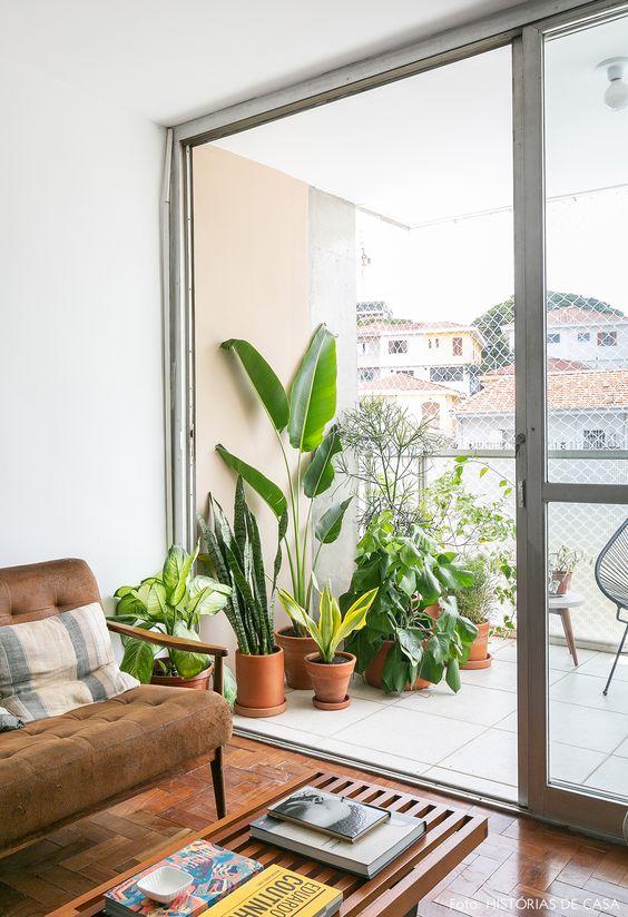 Sala de estar tem banco do designer George Nelson usado como mesa de centro, sofá com desenho vintage e na varanda, plantas em vasos de barro.