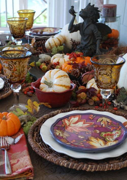An attractive Thanksgiving tablescape... I  really like the goblets (plus, the fairy figure holding the little bird!). Note the little butterfly placed on the napkin - sweet touch!