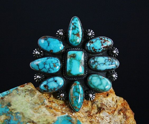 This one of a kind ingot ring created by award winning Navajo artist, Calvin Martinez, features a gorgeous cluster of nine rare high grade natural Carico Lake spiderweb turquoise cabochons mined in the early 1970's. Known as Carico Lake supreme the turquoise has a beautiful deep sky blue hue with shades of both golden and reddish-brown webbing. The ring is made from labor intensive hand rolled and hammered ingot sterling silver with hand twisted wire around the center stone ...:
