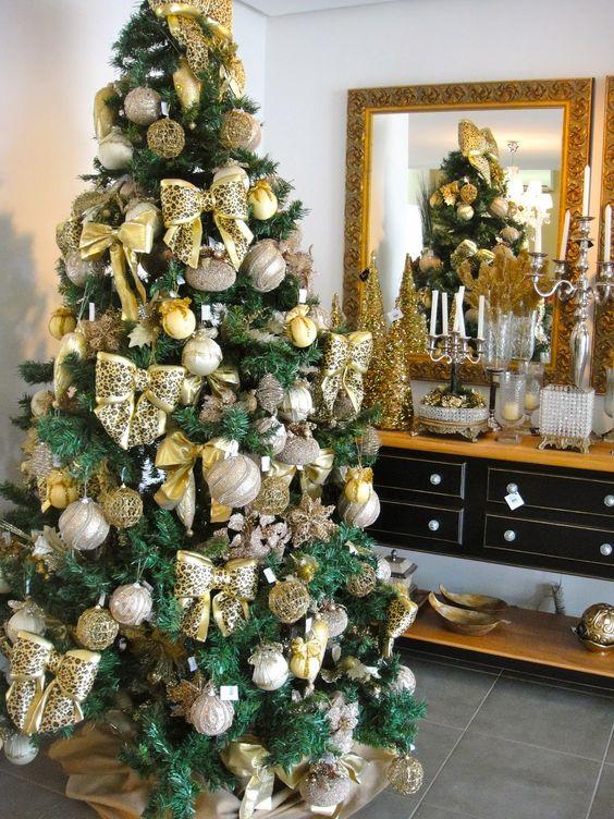 arvore de natal dourada com bolas e laços Mais