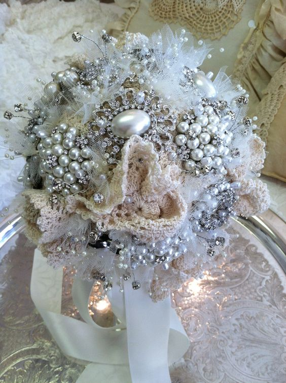 This beautiful vintage inspired bridal bouquet has lots of pearls, bling, lace and doilies! Have your own brooches, earrings, or pearls that are sentimental to you?  Bring them in to Ruby Ellen's and we can design one especially for you for your special day!