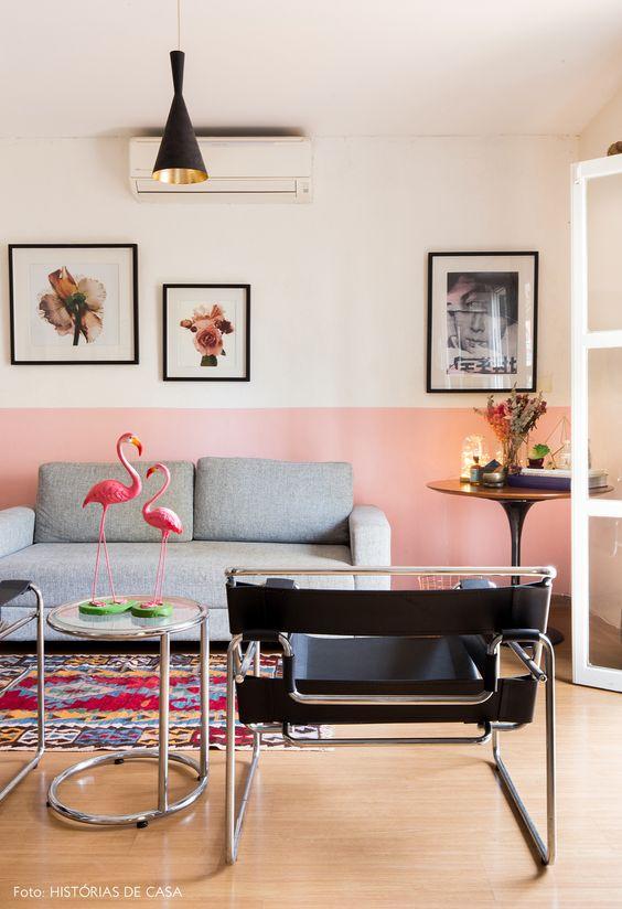 Sala de estar em apartamento alugado tem sofá cinza, poltronas pretas, meia parede pintada de rosa, quadros e plantas.