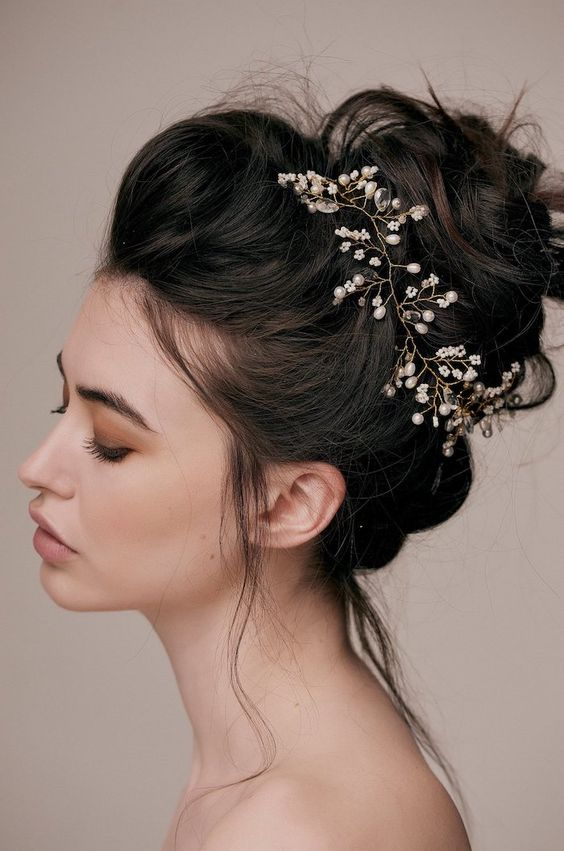 wedding hairstyles for long hair, black hair, in a messy bun, pearl hair accessory, grey background