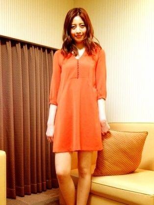 オレンジのワンピースを着てソファーの前に立っている片瀬那奈の画像